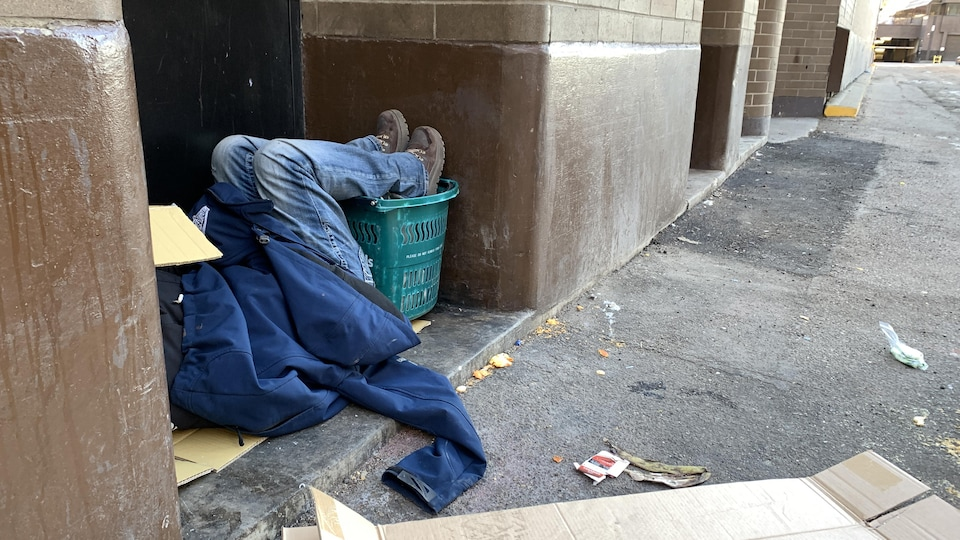 Un homme dort dans une rue du centre-ville d'Edmonton en janvier 2021.