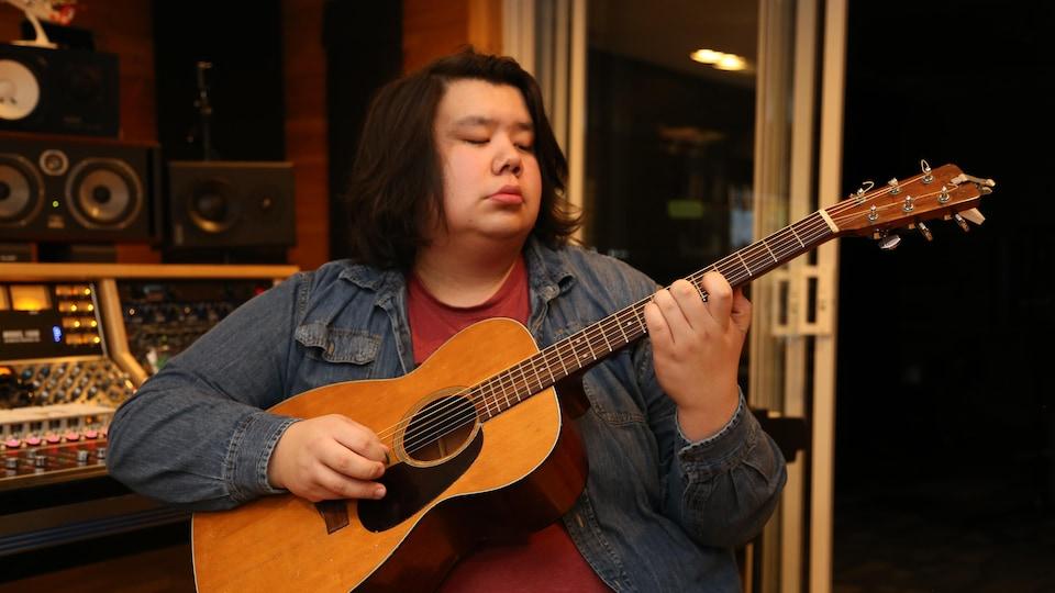 Ivan Boivin-Flamand joue de la guitare.