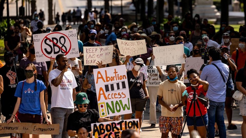 Des manifestantes et des manifestants portent des pancartes en faveur du droit à l'avortement au Texas.
