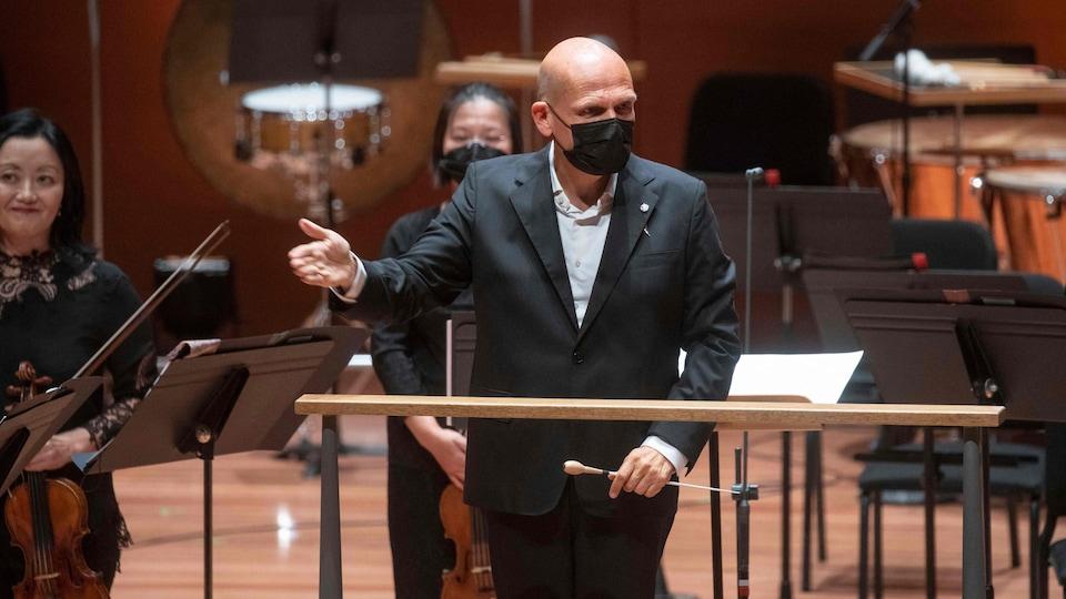 Un homme portant un masque sanitaire s'adresse à la foule devant son lutrin.