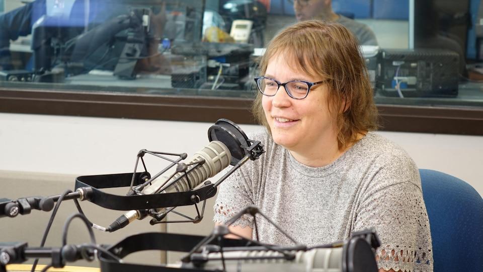 Une femme qui porte des lunettes sourit devant un micro.