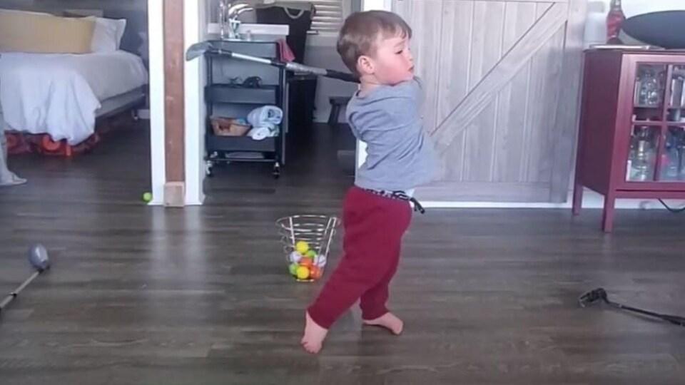 Un enfant tient un bâton de golf.