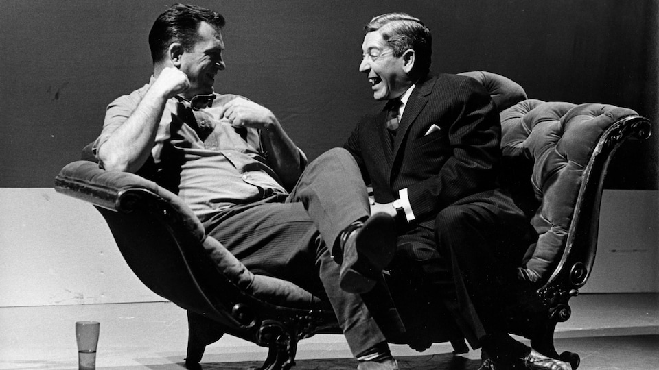 Jack Kerouac et Fernand Séguin qui rigolent assis sur un divan.