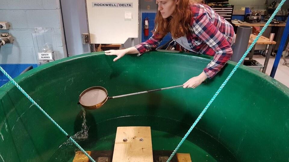 Jackie Saturno avec une passoire au-dessus du bassin utilisé pour son expérience.