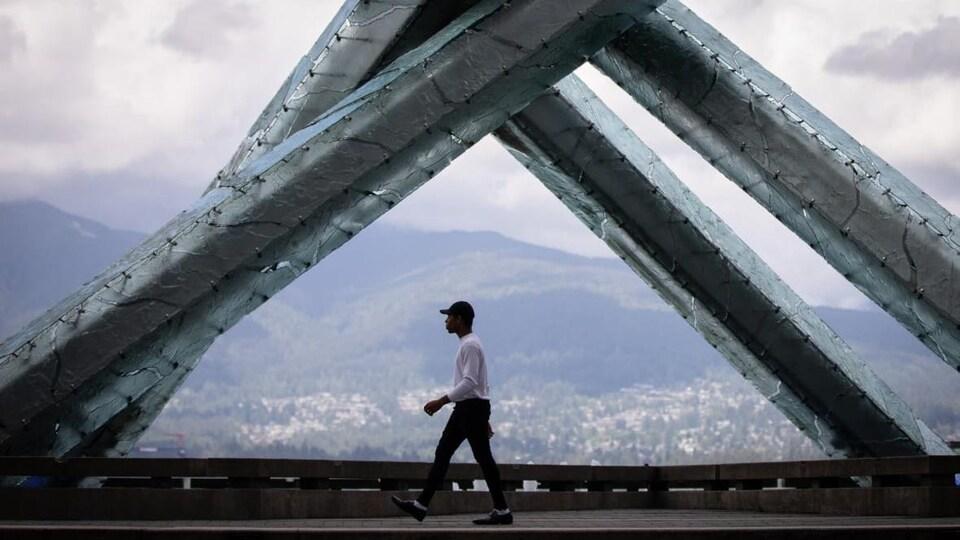 Jacob Callender-Prasad marche devant la vasque olympique, on aperçoit les montagnes derrière.