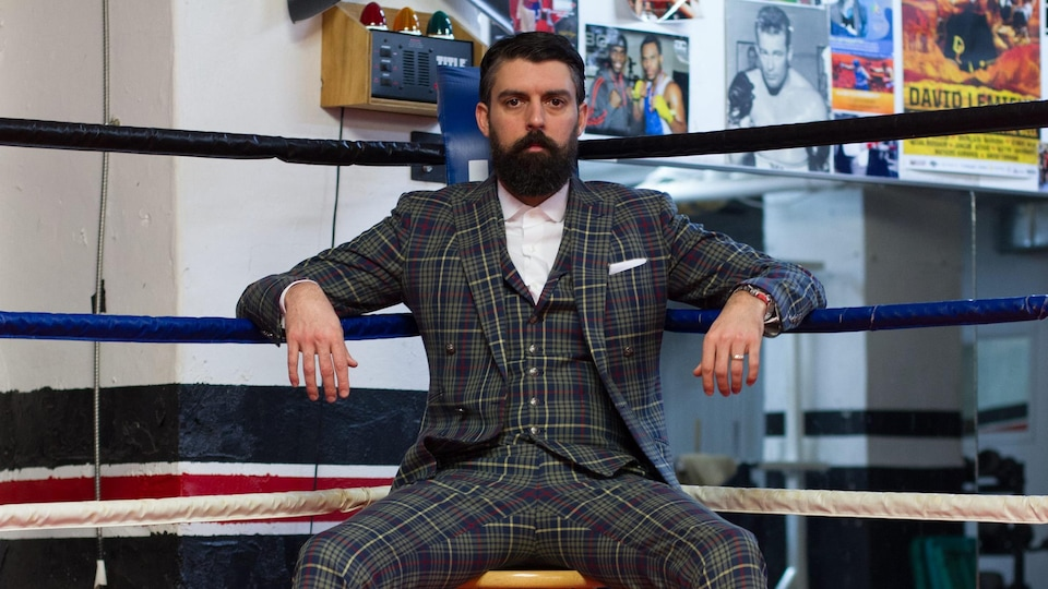 Jacobus en habit, assis dans une arène de boxe.