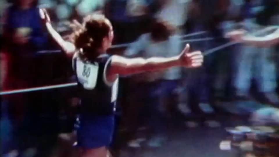 Jacqueline Gareau, de dos avec son dossard de course, les bras en l'air en courant.