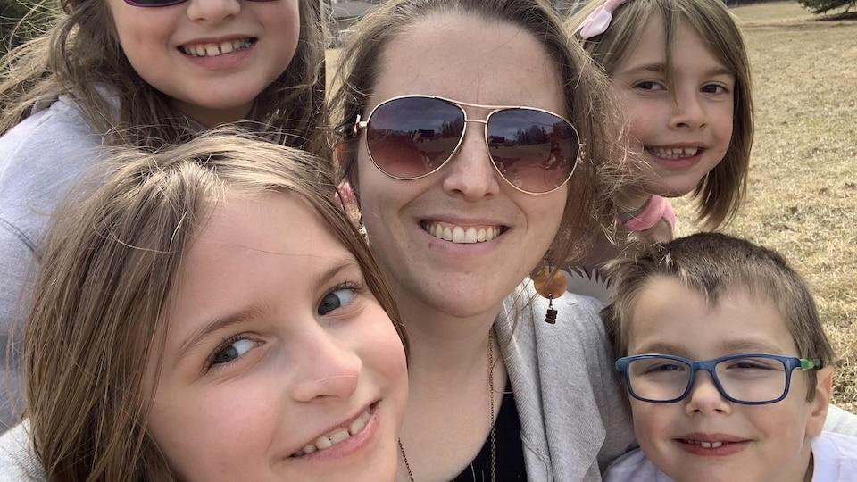Une femme et quatre enfants sourient devant la caméra.