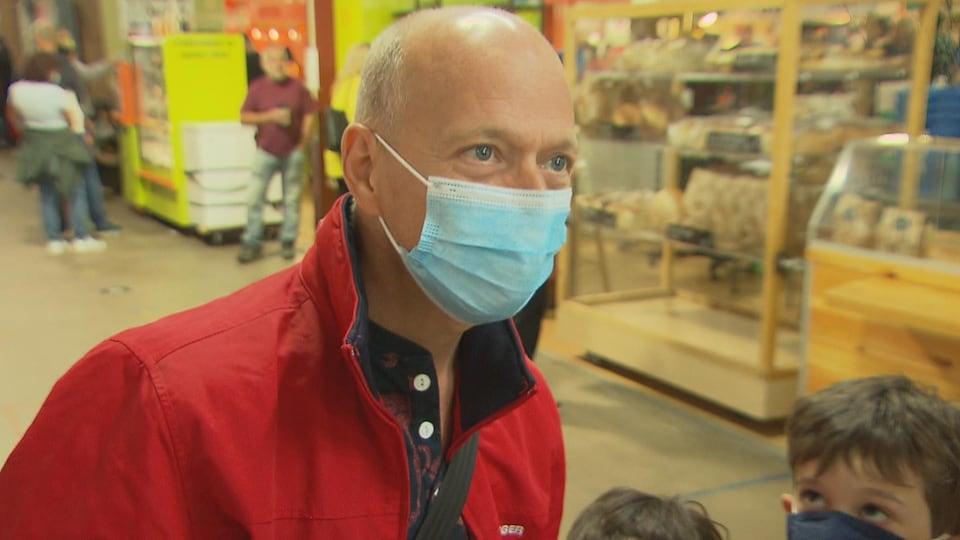 Un homme au visage couvert d'un masque se tient debout entre des étalages aux côtés de deux enfants, dont un est aussi masqué.