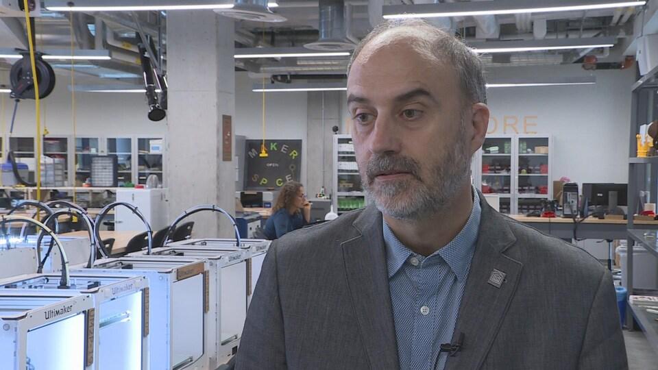 Jacques Beauvais en entrevue dans un laboratoire où l'on retrouve de nombreuses imprimantes 3D.