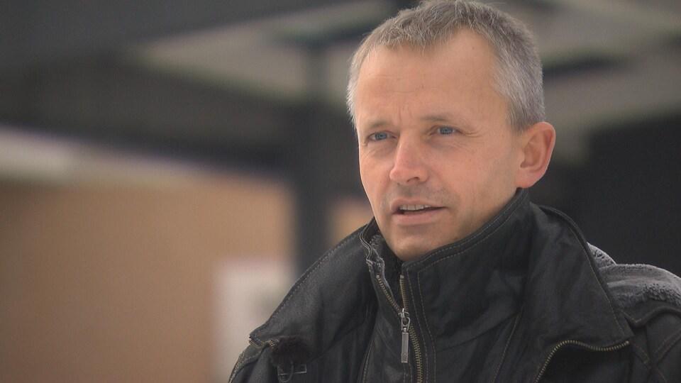 Jacques Cherblanc en position d'entrevue, regarde au loin.