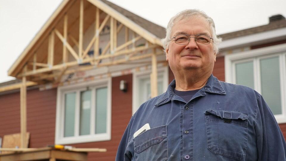Un homme devant une maison en construction. Il porte des lunettes.