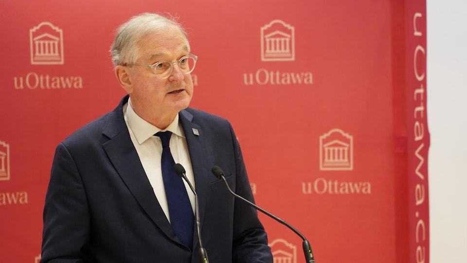 Jacques Frémont prend la parole derrière un lutrin avec derrière lui une toile comptant de nombreux logos de l'Université d'Ottawa.