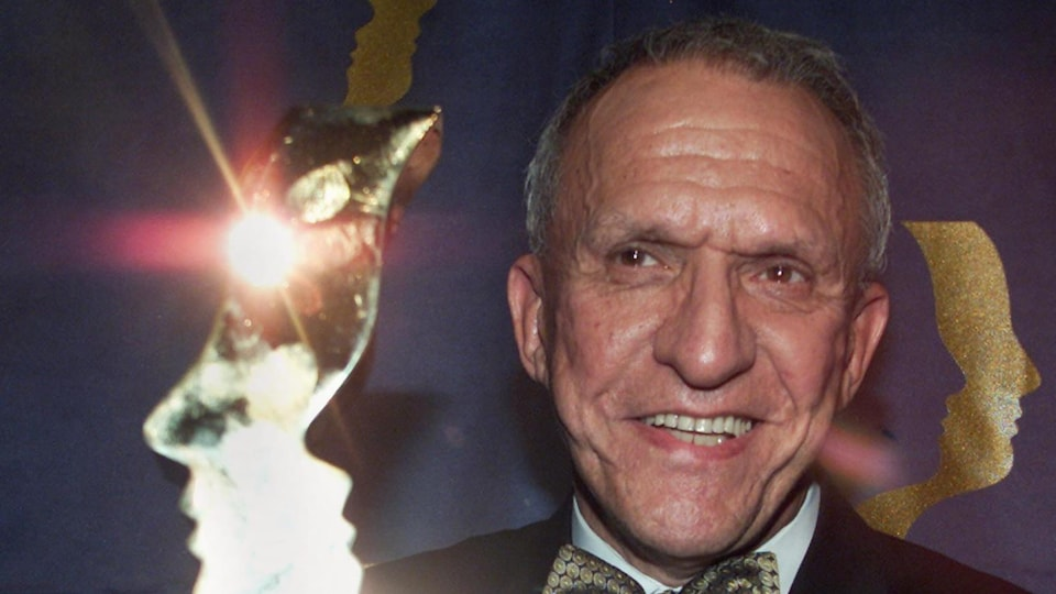 Jacques Godin, très souriant, tend son trophée.