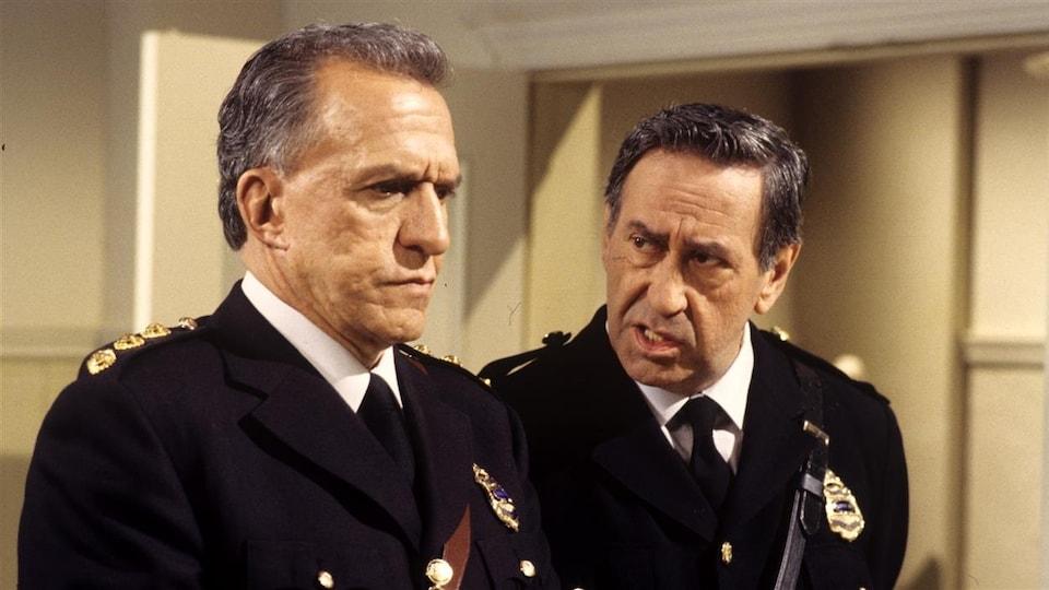 Jacques Godin, habillé en policier, écoute un autre agent.