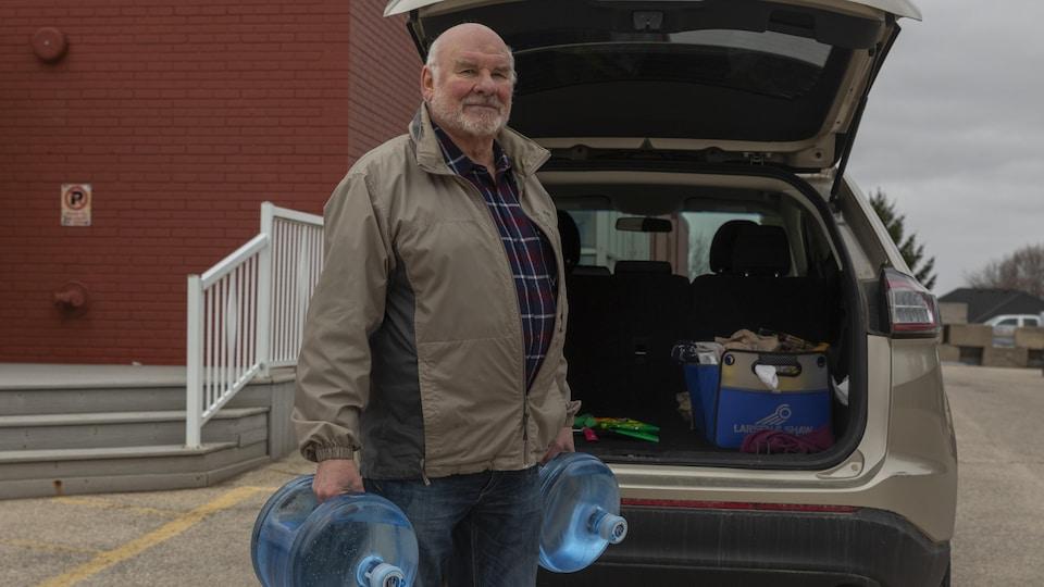 Un homme debout avec des bidons d'eau.