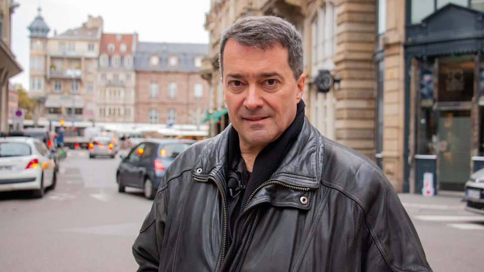 Jacques Lacombe qui regarde la caméra, dans les rues de Strasbourg