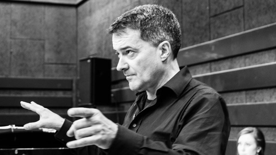 Jacques Lacombe, de côté, qui dirige des chanteurs lors d'une répétition.