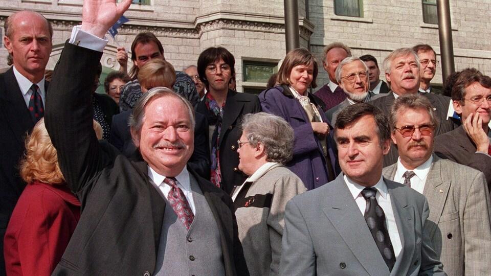 Jacques Parizeau et Lucien Bouchard devant plusieurs partisans, à l'extérieur, un jour d'automne. M. Parizeau salue la foule, qu'on image devant lui.