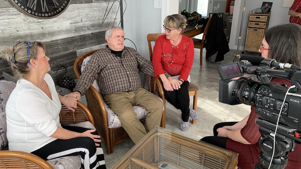 Un homme accorde une entrevue à Annie-Claude Luneau, tenant ses deux soeurs par la main.