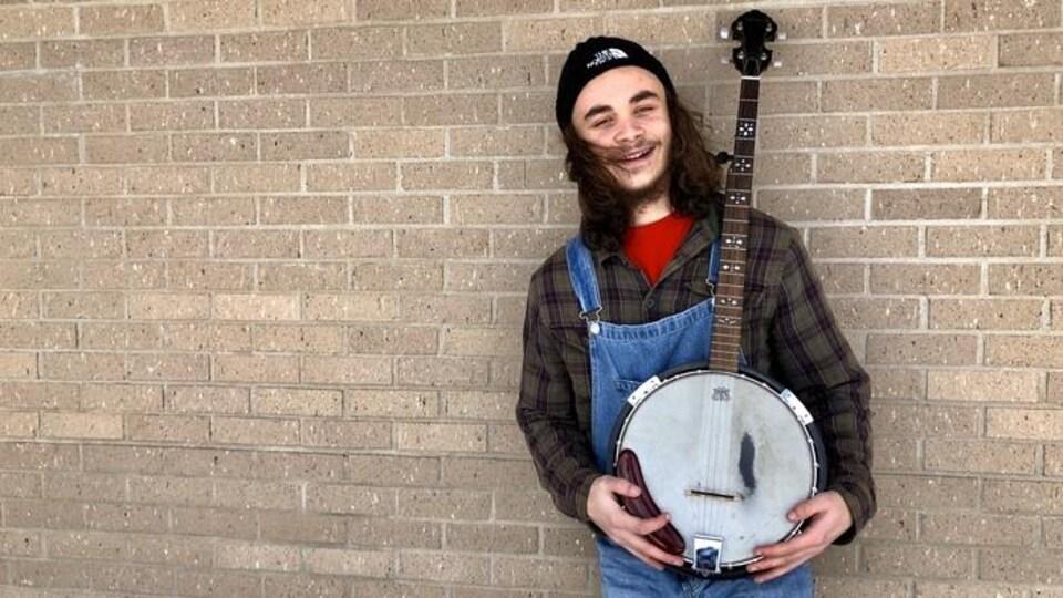 Un jeune homme de 19 ans synpathique en saloppette souri à la camera avec son banjo dans les mains.