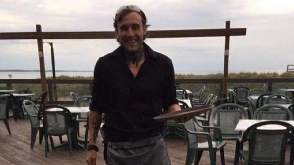 Un barman sur une terrasse, un plateau à la main.