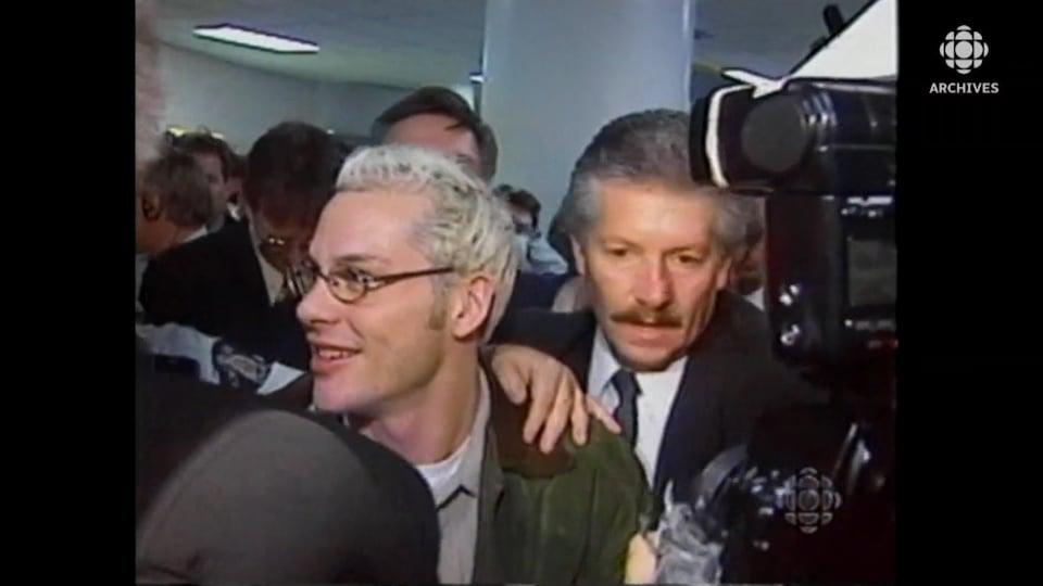 Jacques Villeneuve se frayant un chemin parmi la foule et les médias à l'aéroport.