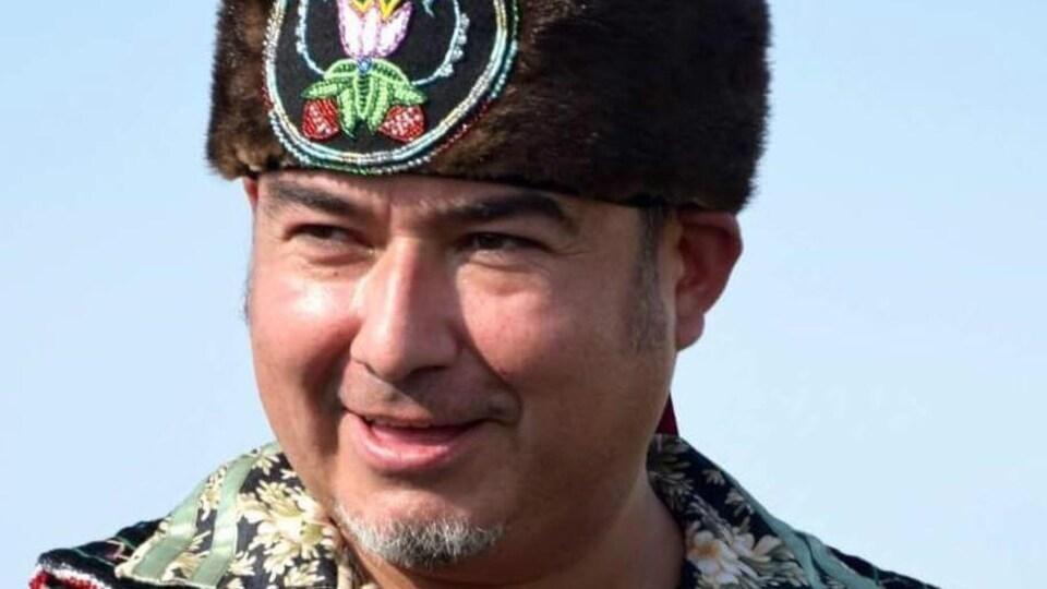 Un homme porte un chapeau traditionnel autochtone.
