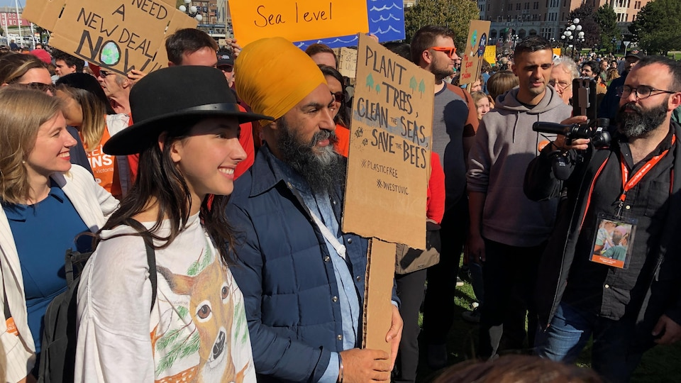 Jagmeet Singh brandissant une pancarte sur laquelle on lit : « Plant trees, clean the seas, save the bees » (Plantez des arbres, nettoyez les mers, sauvez les abeilles).