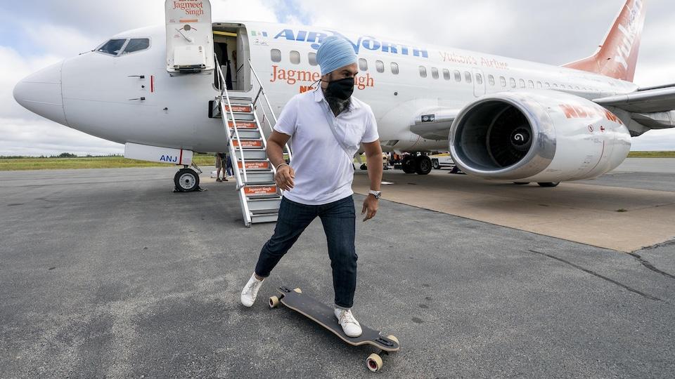 Jagmeet Singh sur un long board devant un avion.