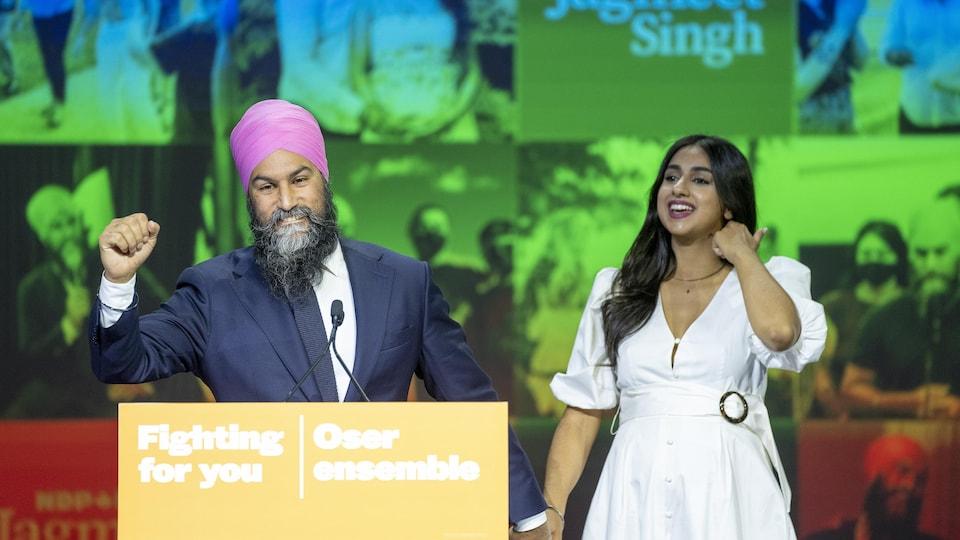 Jagmeet Singh lève le poing en souriant. Il tient la main de son épouse devant un podium où est écrit le slogan « Fighting for you; Oser ensemble ».