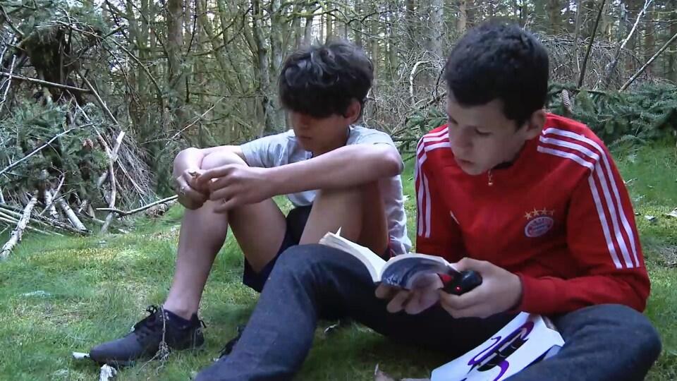 Deux garçons assis sur le sol, dont l'un lit un livre.