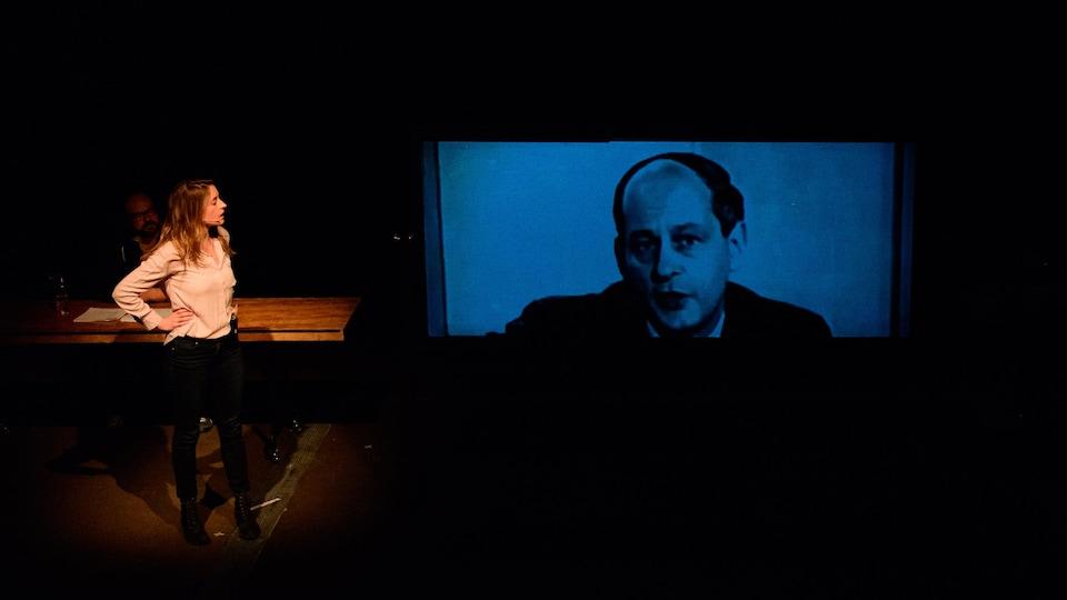 La comédienne regarde une image de René Lévesque qui apparait sur un écran
