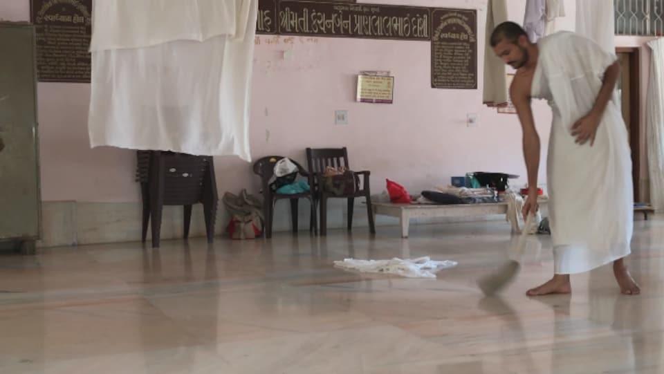 Un moine jaïn montre comment il utilise un balai pour éviter de tuer des insectes en marchant.