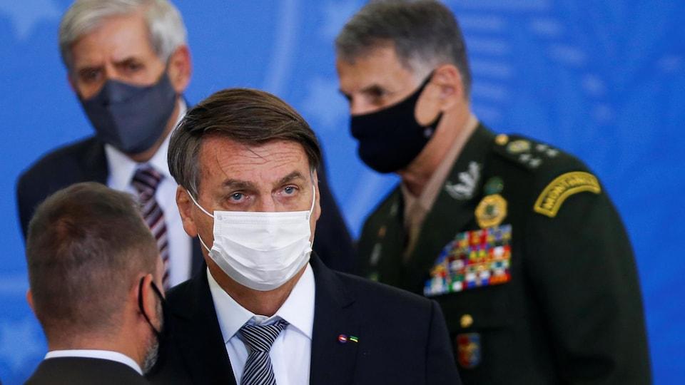 M. Bolsonaro, masqué, écoute un homme planté devant lui.