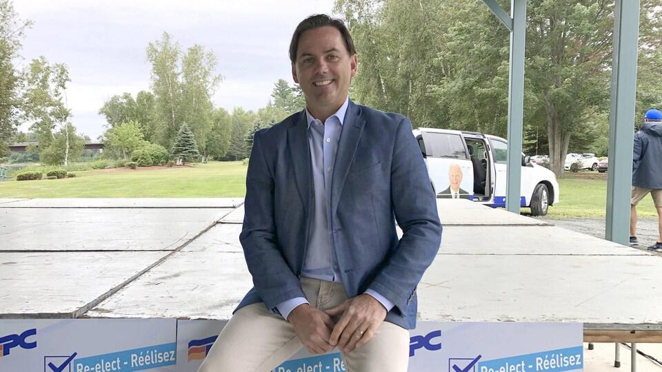 Jake Stewart assis sur le rebord d'une table décorée de ses affiches de campagne électorale.