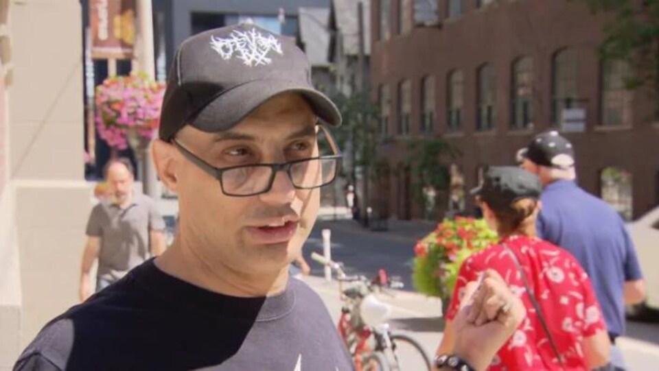 James Cavalluzzo porte une casquette noire, il semble rasé en-dessous, il a des lunettes à monture noire également. Il est dehors, proche d'une piste cyclable.