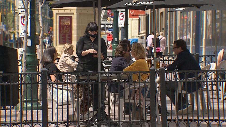 Une serveuse avec un masque sert des clients sur une terrasse du centre-ville de Calgary. Il y a 7 clients qui profitent du temps plus chaud.