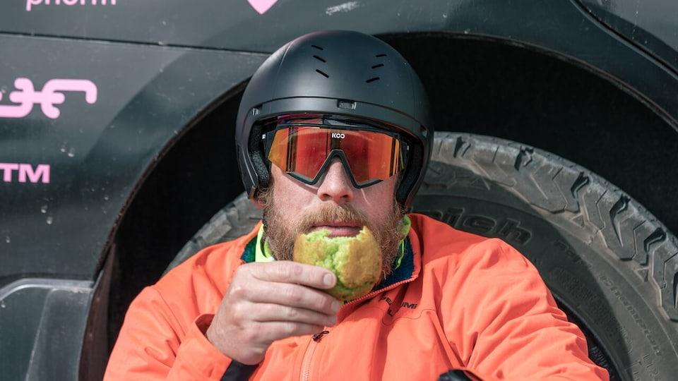 James Lawrence assis et appuyé contre une roue de voiture mangeant un gâteau.