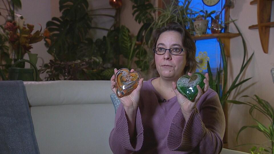 Jamie Johnston tient dans ses mains deux coeurs en verre qu'elle a fait faire avec les cendres du père biologique de ses enfants.