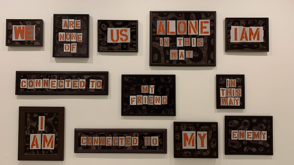 Une série de cadre avec des mots sur mur.