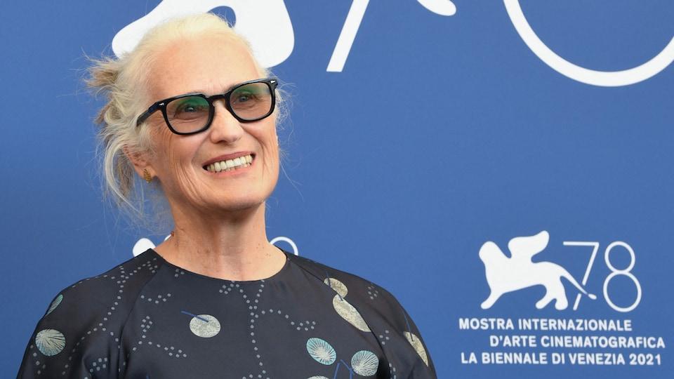La femme sourit en posant pour les photographes devant un mur bleu avec le logo de la Mostra.