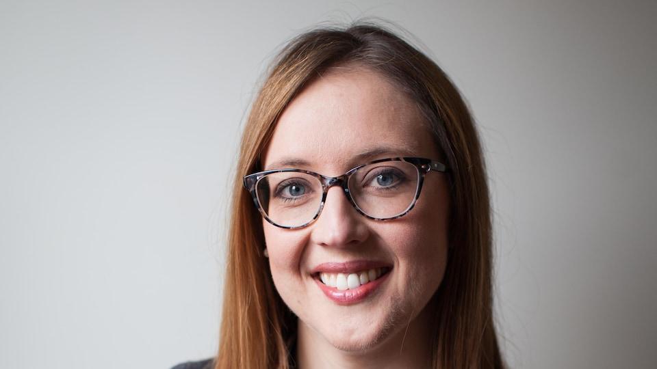 Jane Hilderman sourit à la caméra devant un fond neutre blanc. Elle porte des lunettes.