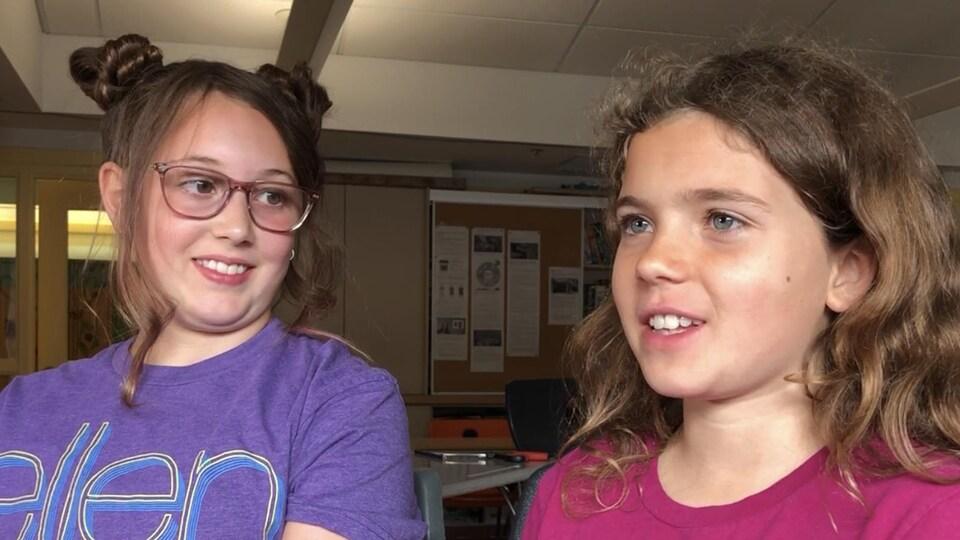 Deux filles s'adressent à la caméra, elles sont assises dans une salle de classe.