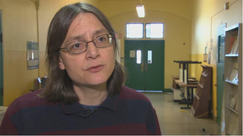Une femme s'adressant à la caméra.