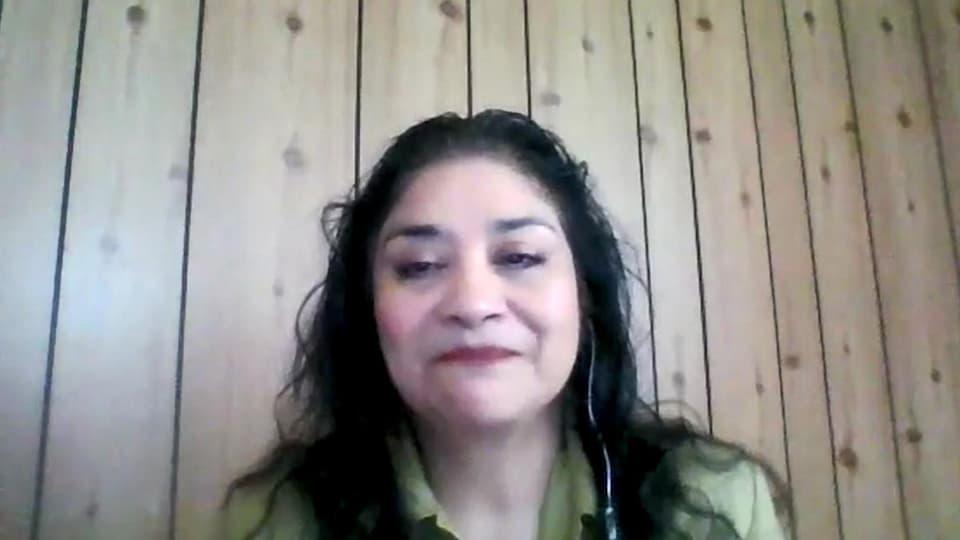 Capture d'écran d'une vidéoconférence : Janet Rodriguez assise devant un mur en bois.