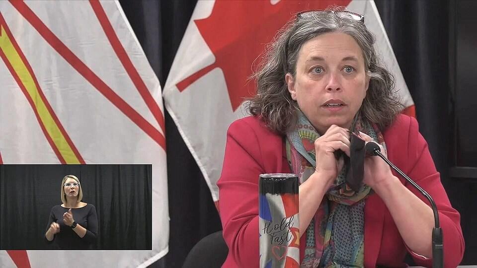 Janice Fitzgerald tient son masque entre ses mains pendant qu'elle répond à une question en conférence de presse.