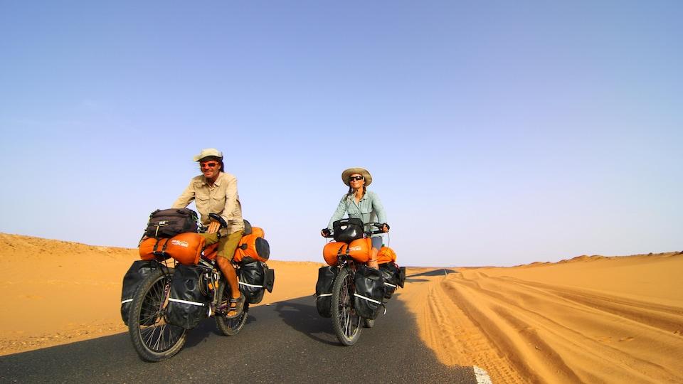Janick Lemieux et Pierre Bouchard sont à vélo sur une route au milieu du désert.
