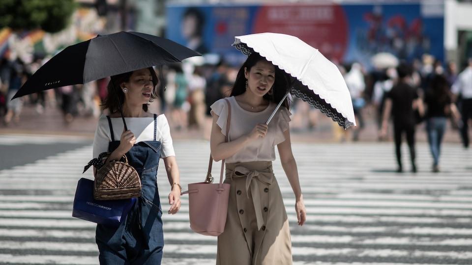 Des Asiatiques tiennent des parapluies dans leur main alors qu'elles traversent la rue. Des rayons de soleil qui semblent chauds frappent leur parapluie.