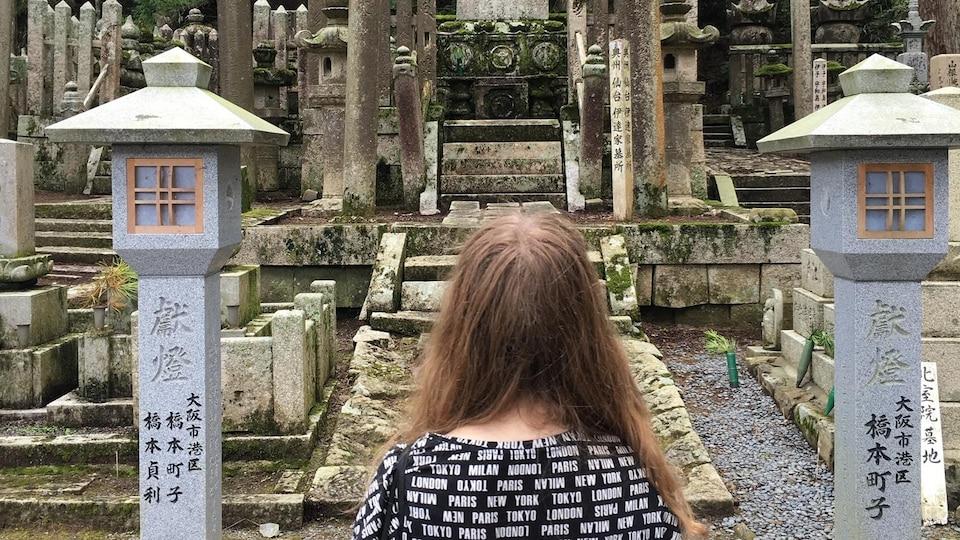 Une femme vue de dos regarde un petit  temple bouddhiste entourée de verdure devant elle.